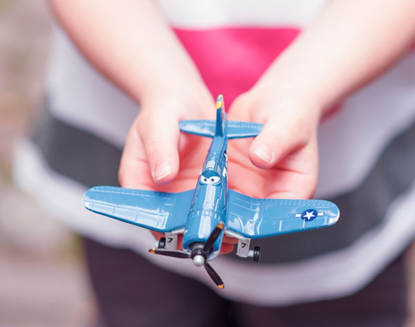 Child holding a toy airplane with both hands.