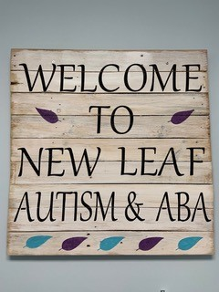 Welcome to New Leaf wooden entry sign.